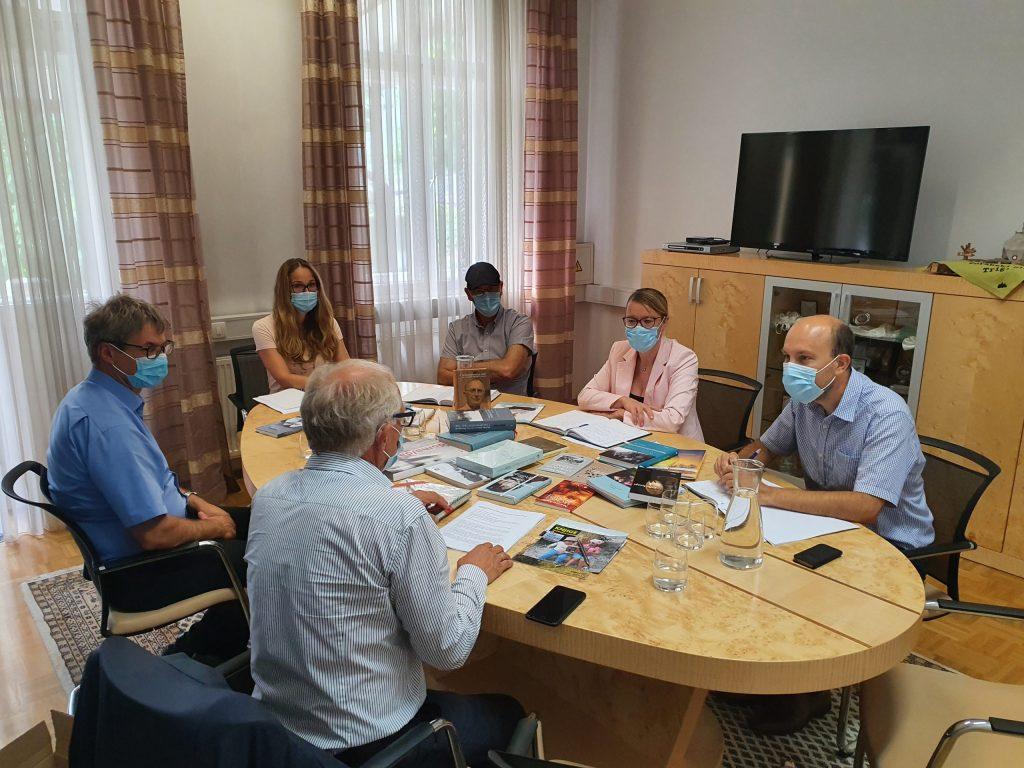 Udeleženci med sestankom na kateri so knjige.