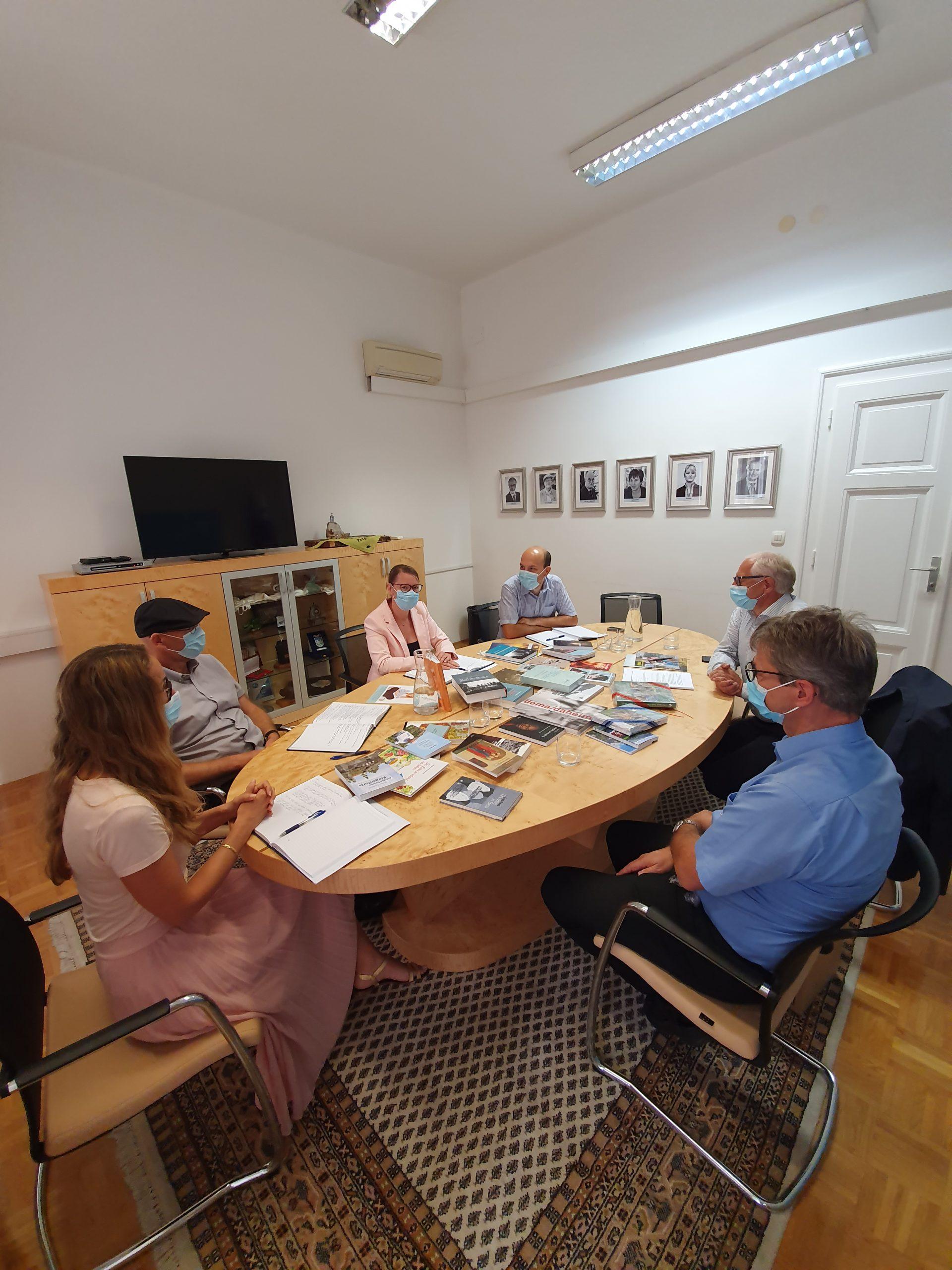 Udeleženci med sestankom za mizo, na kateri so knjige, ki so jih predstavili.