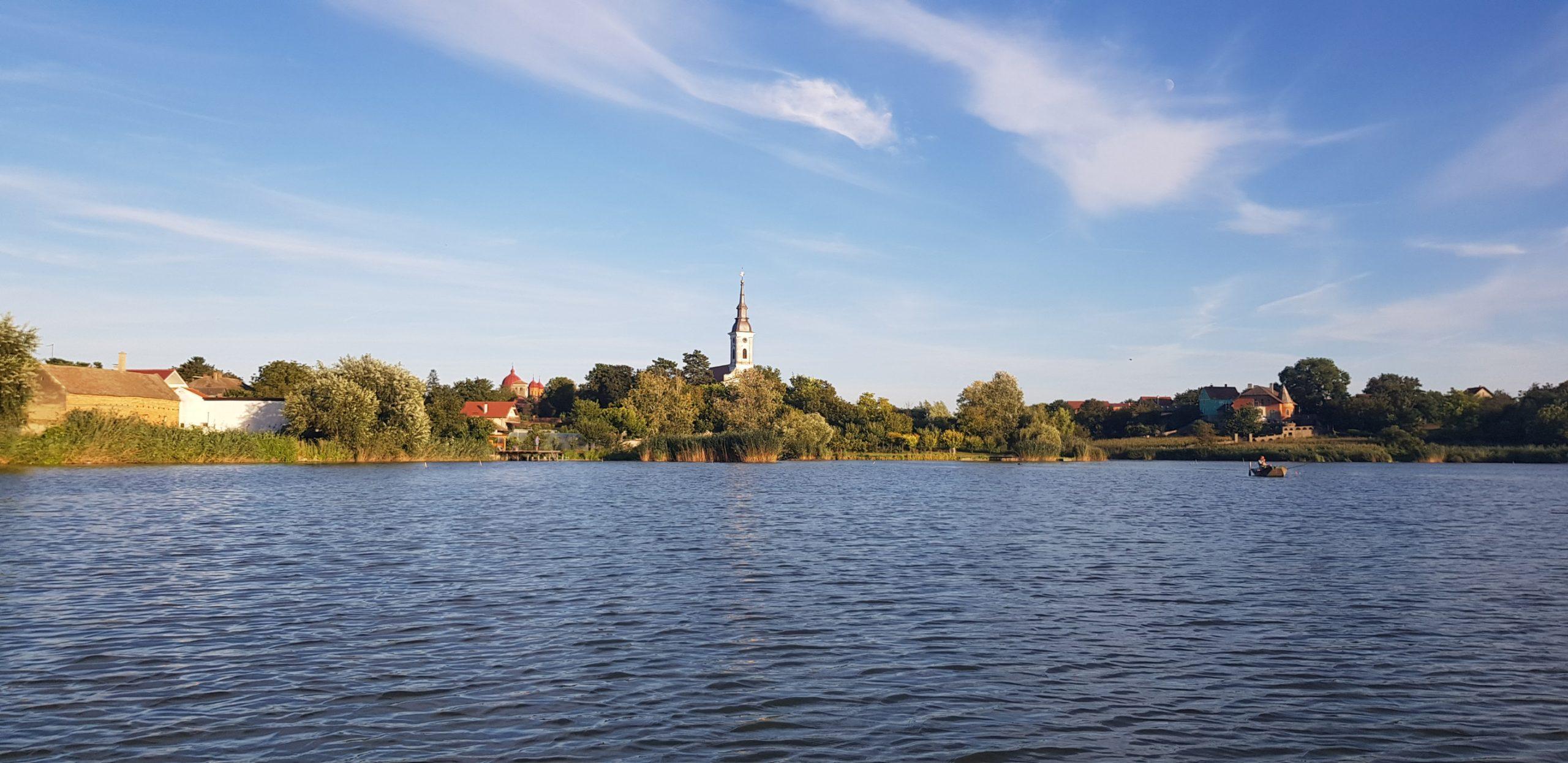 Lokacija (jezero in v ozdaju drevesa in hiše).
