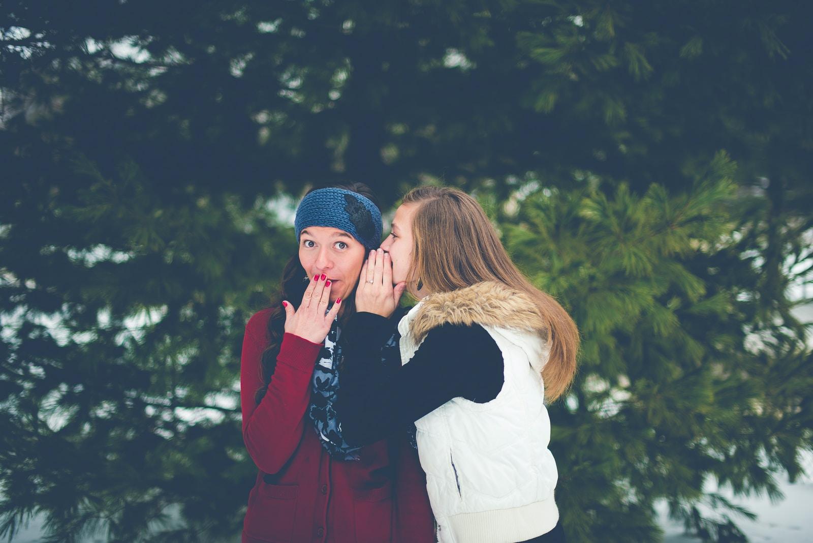 Eno dekle drugi šepeta na uho.