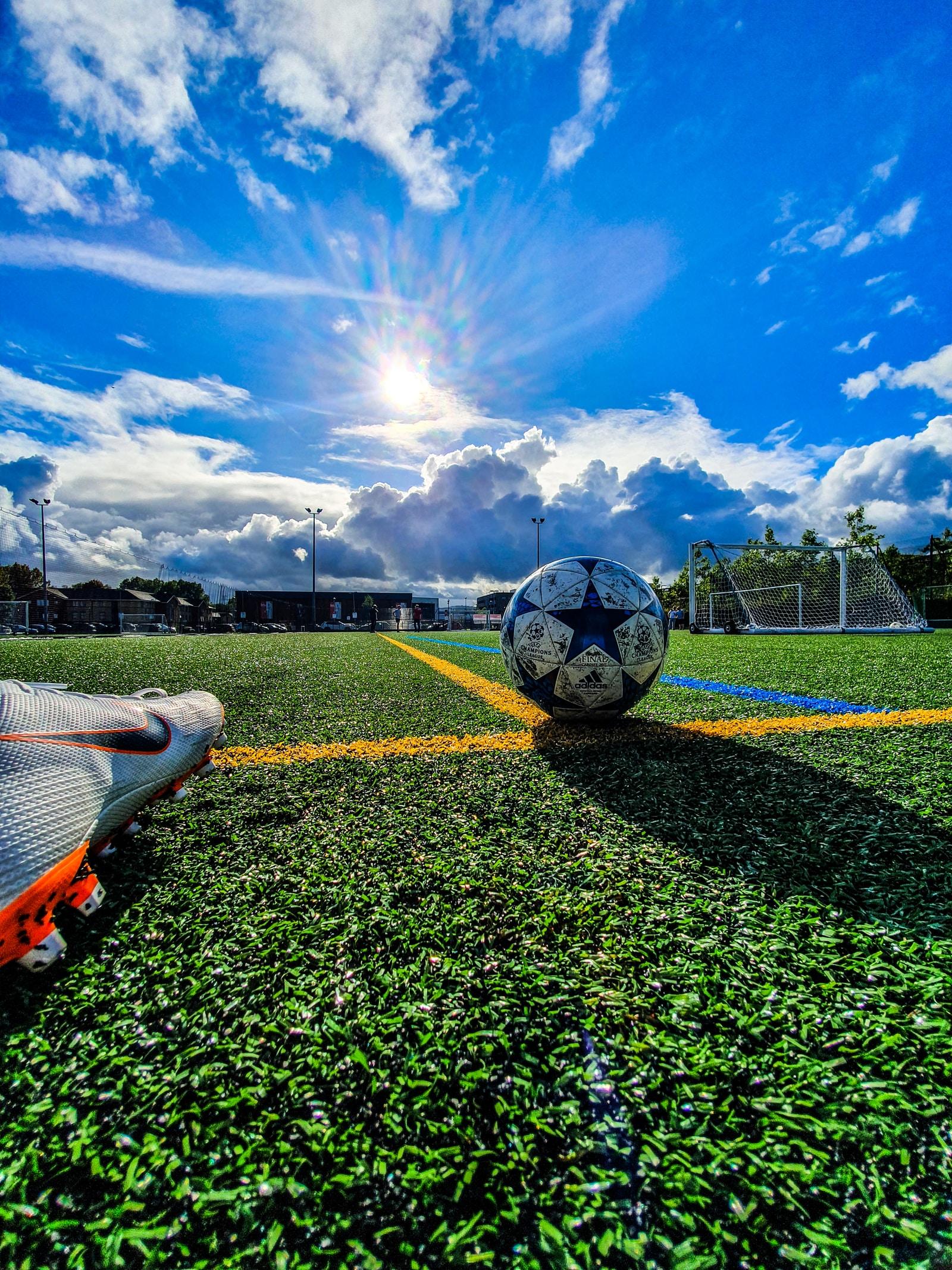 Žoga na nogometnem igrišču, noga igralca, nebo z oblaki in soncem.