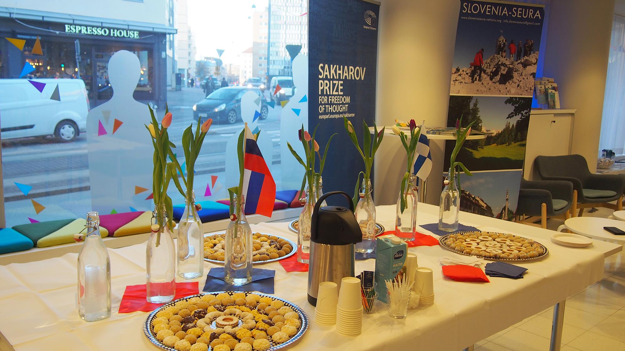 Pogostitev. Miza z dobrotami, svetjem in slovensko zastavo.