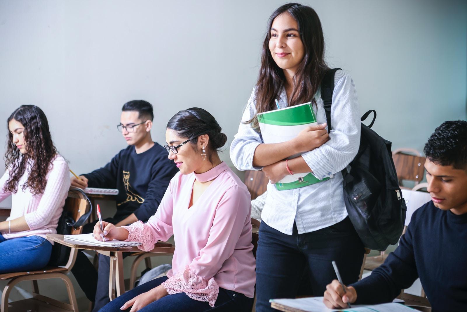 Dekle z zvezkom v roki v razredu, okoli še več študentov sedi za svojimi mizami.