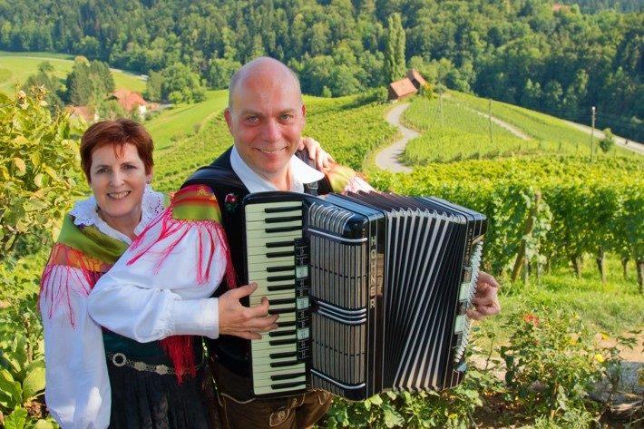 Gospa in gospod v slovenskih narodnih nošah, gospod ima harmoniko, v ozadju pokrajina v Sloveniji.