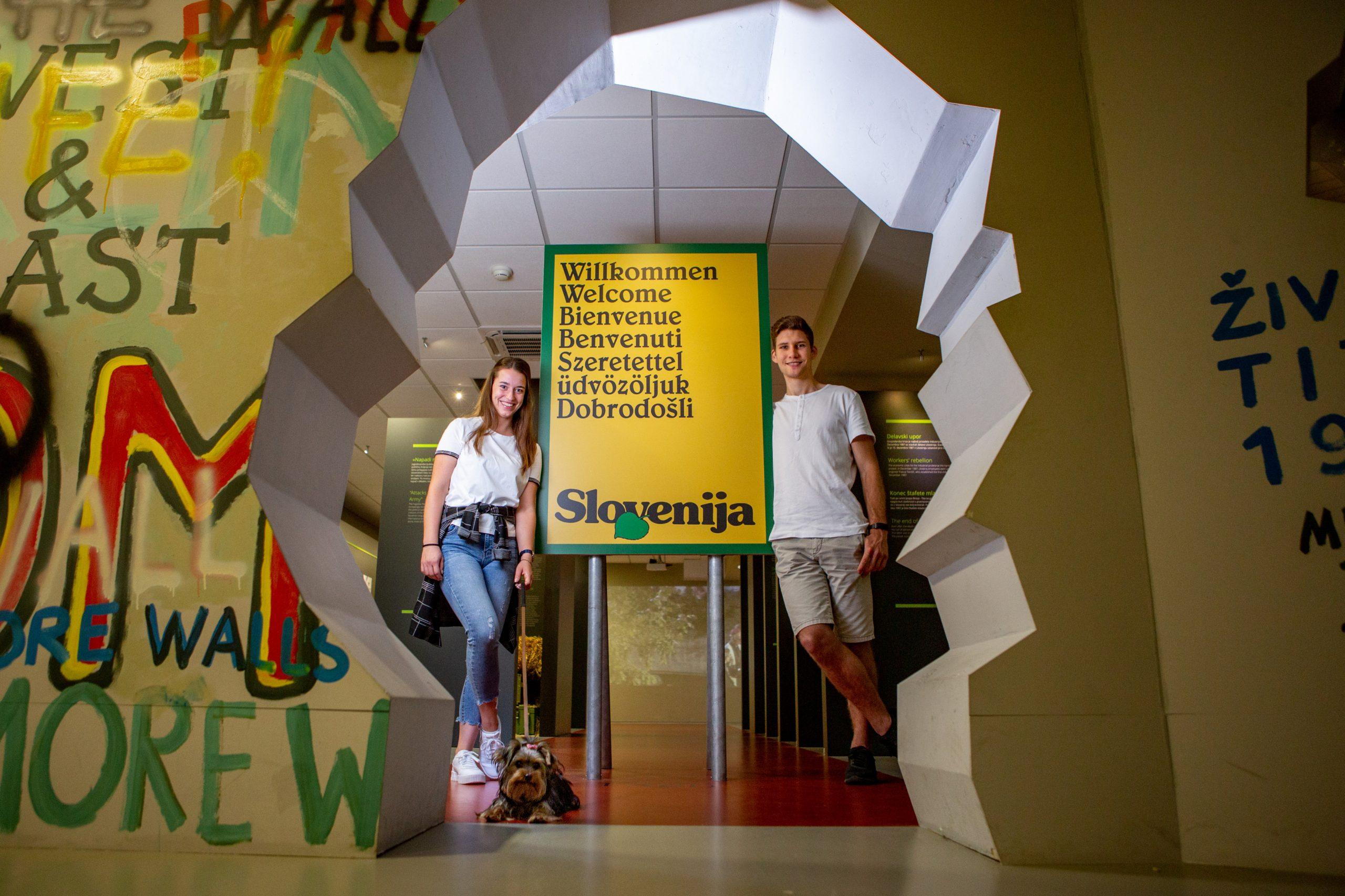 Par v muzeju, pred znakom s časa osamosvojitve.