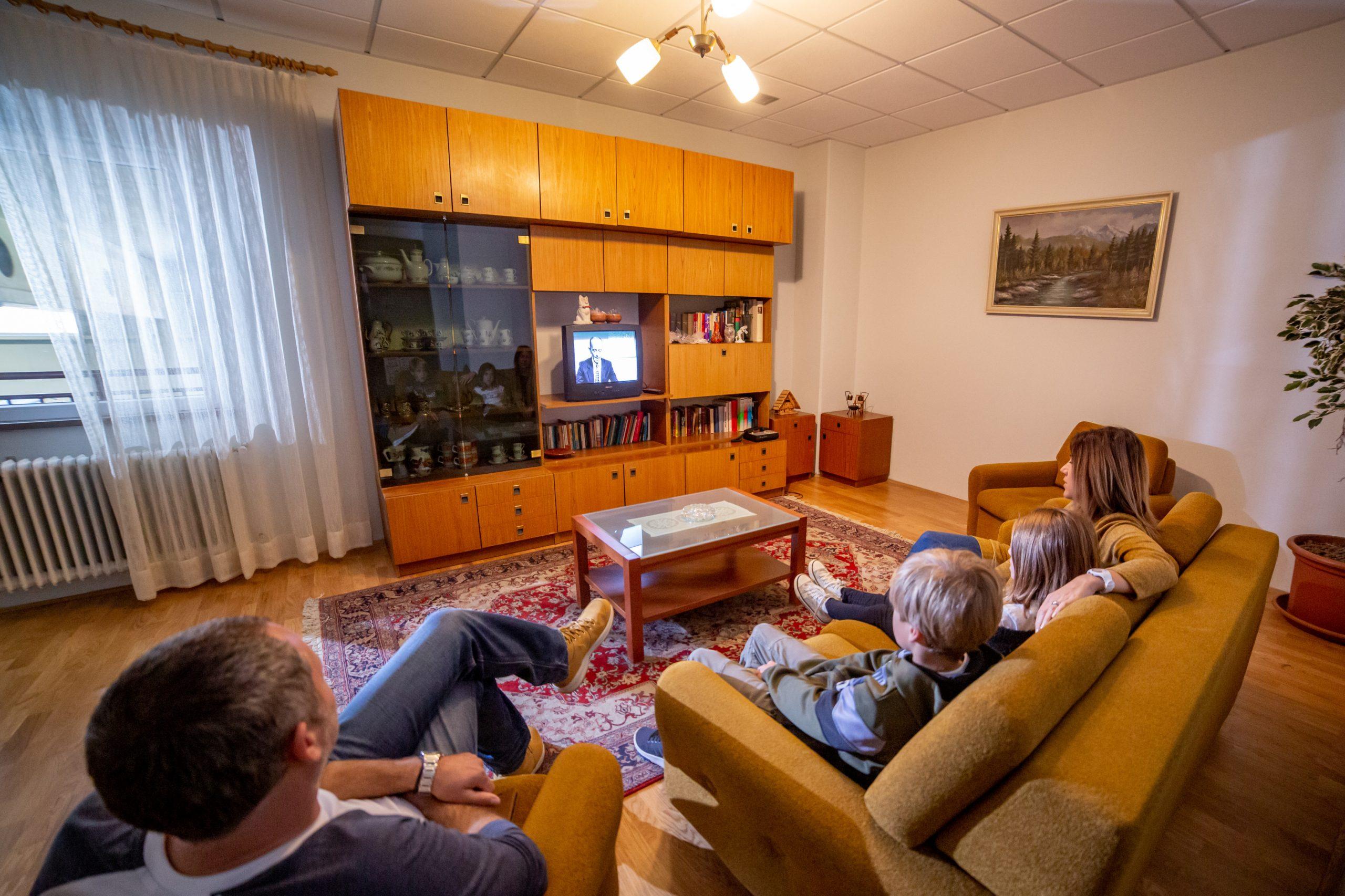 Družina med ogledom. Na kavču pred televizorjem.