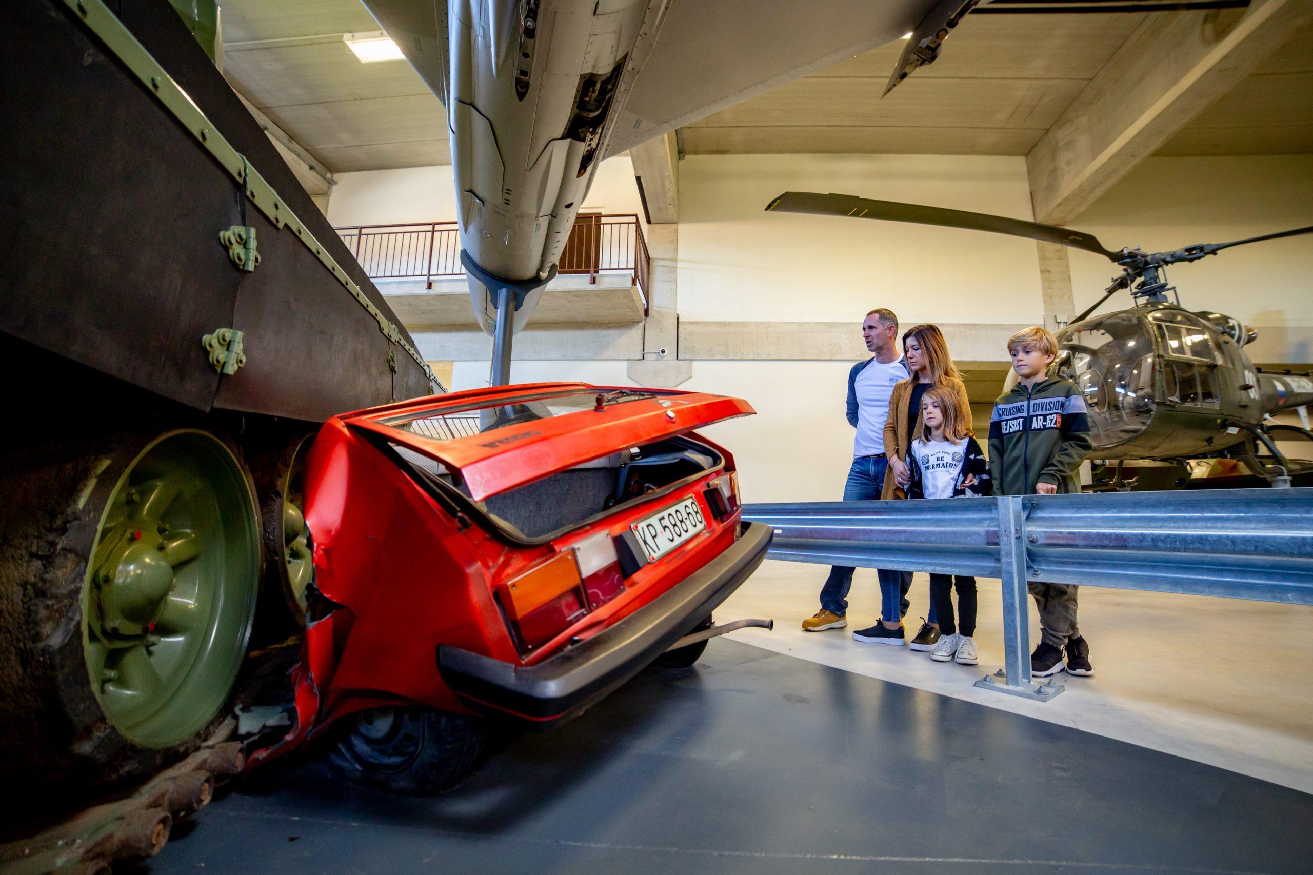 Družina v muzeju, ogleduje si prikaz, kako je tank zmečkal rdeči avtomobil znamke jugo.