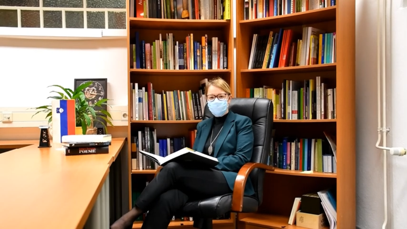 Ministrica s knjigo v roki sedi v knjižnjici.