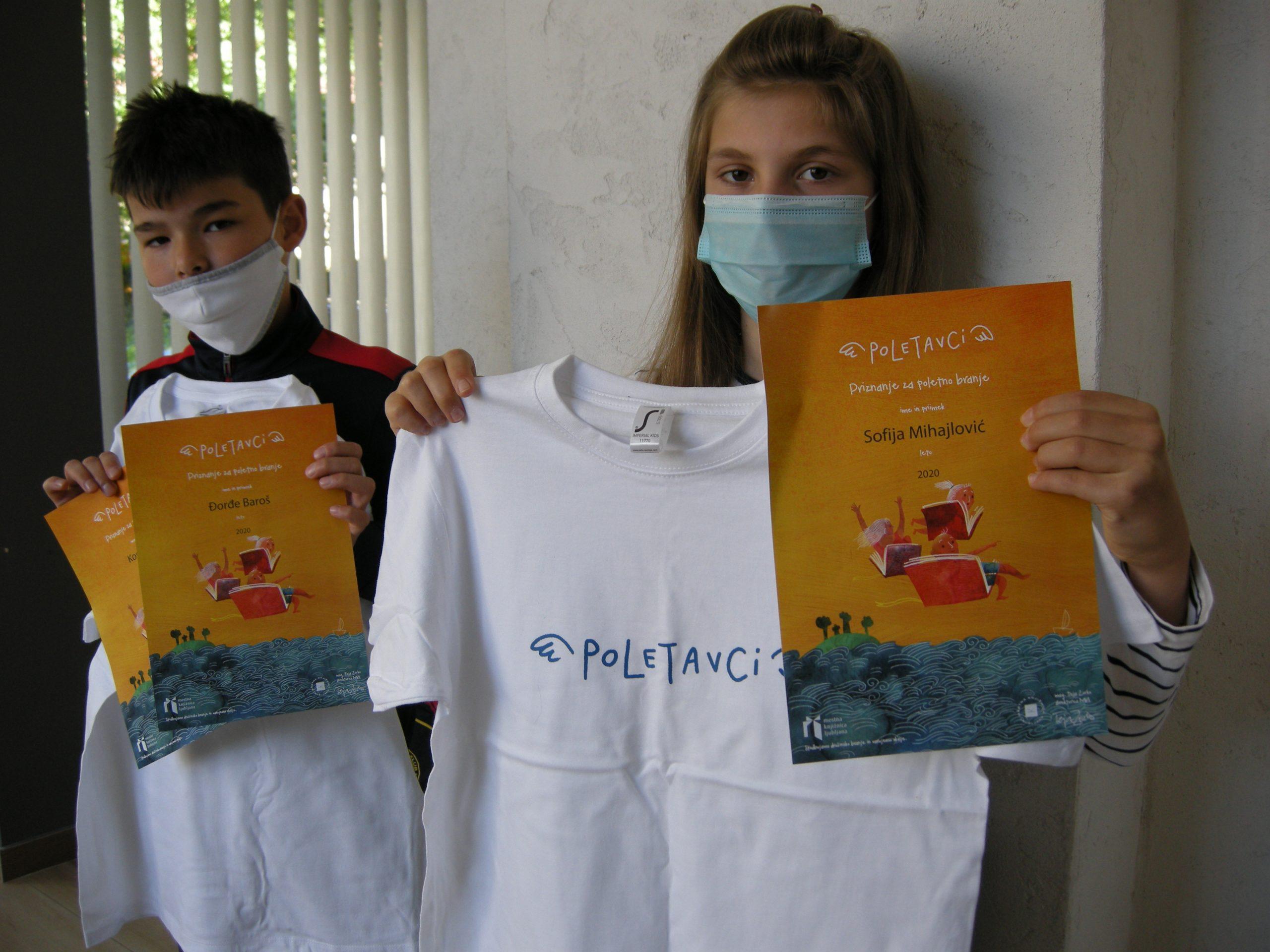 Učenca s priznanjema in z majicama.