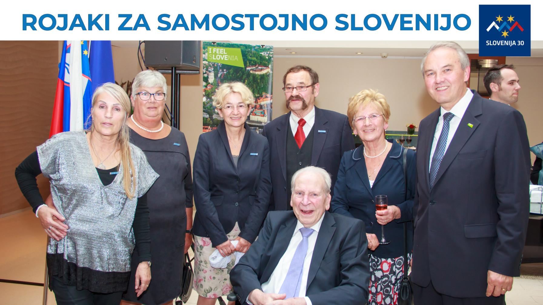 Člani komiteja (na vrhu na belem traku napis Rojaki za samostojno SLovenijo in logo (simbolj Triglava v beli, modri in rdeči barvi, tri rumene zvezde in pod tem napis Slovenija 30).